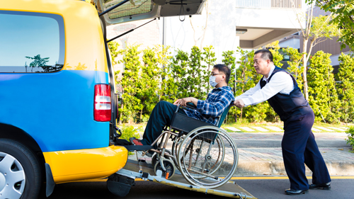 Man helping passenger on wheelchair getting on vehicle